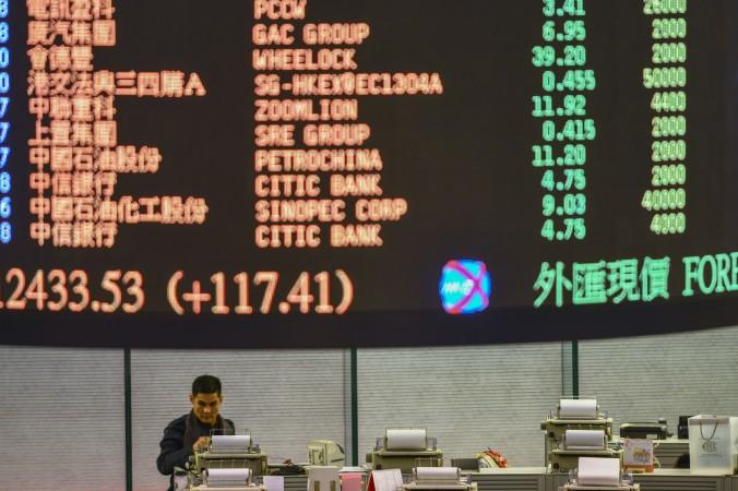 Трейдер просматривает данные на Гонконгской фондовой бирже 2 января 2013 года. Акции двух компаний на Гонконгской фондовой бирже недавно потеряли в течение дня более 40% своей стоимости. Фото: Antony Dickson/AFP/Getty Images | Epoch Times Россия