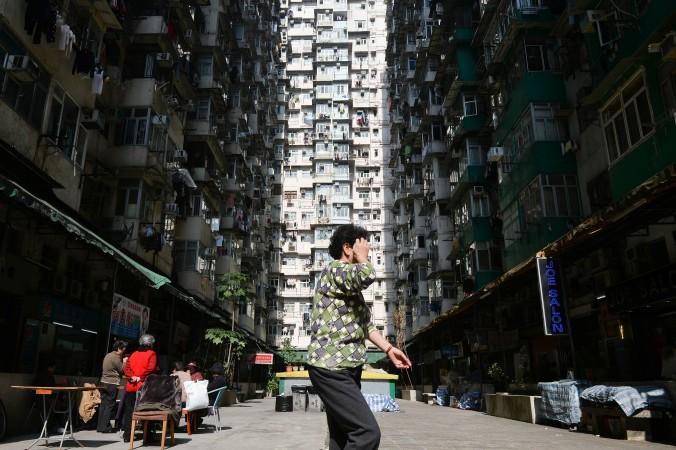 Женщина в жилом районе Гонконга 30 декабря 2013 года. Рынок недвижимости Китая прекратил падать в апреле, но ситуация остаётся нестабильной. Фото: Dale de la Rey/AFP/Getty Images | Epoch Times Россия