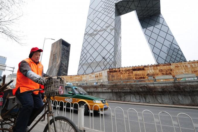 Дворник едет мимо здания центрального телевидения CCTV в Пекине 28 февраля 2010 года. Фото: FREDERIC J. BROWN/AFP/Getty Images   Epoch Times Россия