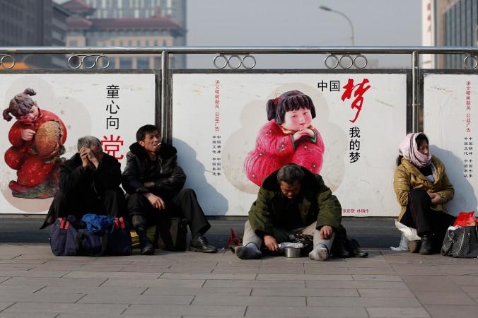 Нищий сидит на фоне плаката с правительственной пропагандой на железнодорожном вокзале Пекина 2 марта 2014 года. Развитые страны стараются расширить свой средний класс, yо в Китае это не было достигнуто. Фото: Lintao Zhang/Getty Images   Epoch Times Россия