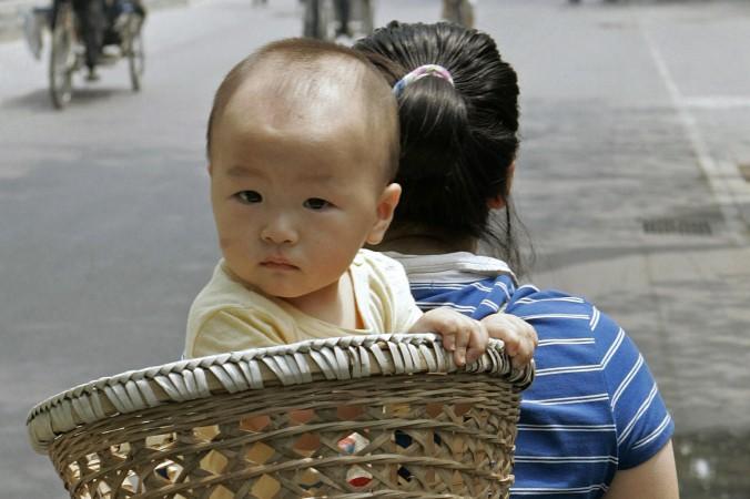Мать несёт ребёнка в корзине на спине, Пекин, июнь 2007 г. Партийные чиновники в провинции Шаньдун недавно нашли способ выполнять квоты по принудительным абортам. Фото: Peter Parks/AFP/Getty Images   Epoch Times Россия