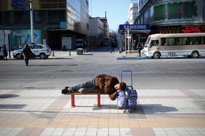 Старик отдыхает на скамейке в Пекине 3 января 2014 г. Фото: Wang Zhao/AFP/Getty Images | Epoch Times Россия
