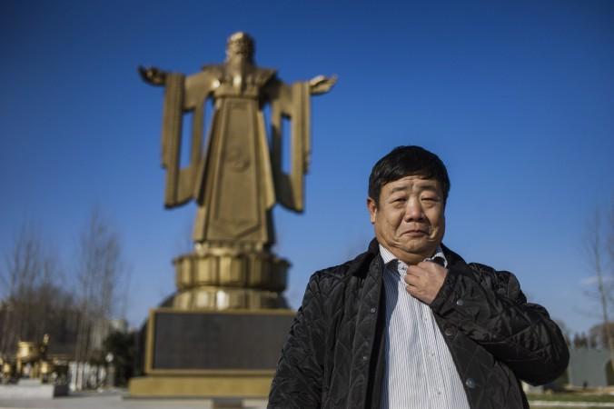 Китайский генерал в отставке Ван Дианьмин стоит рядом со статуей Конфуция в курортном городе Бэйдайхэ, провинция Хэбэй, 12 декабря 2014 г. Фото: Fred Dufour/AFP/Getty Images | Epoch Times Россия