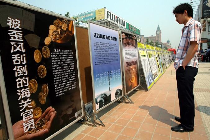 Китаец рассматривает стенды с антикоррупционными лозунгами 11 июня 2007 года. Фото: Teh Eng Koon/AFP/Getty Images | Epoch Times Россия