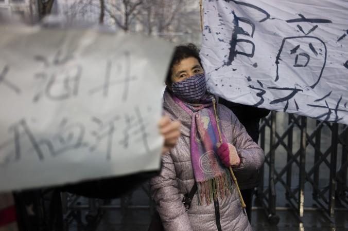 Женщина протестует против злоупотреблений местных властей и невыплаченных зарплат у здания суда Ланфан 10 декабря 2014 года. Фото: Fred Dufour/AFP/Getty Images | Epoch Times Россия