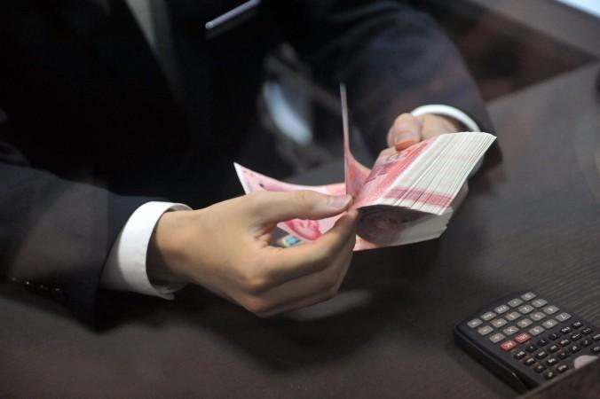 Сотрудник отсчитывает банкноты в 100 юаней в банке в Ханчжоу, провинция Чжэцзян Восточного Китая, 1 декабря 2015 г. Фото: STR/AFP/Getty Images | Epoch Times Россия