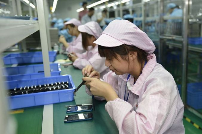 Сборка смартфонов Apple в Китае. Фото:  STR/AFP/Getty Images | Epoch Times Россия