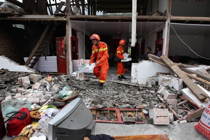 Спасатели помогают достать ценные вещи из повреждённого после землетрясения дома в уезде Лушань, г. Я-ань, провинция Сычуань на юго-западе Китая. 21 апреля 2013 года. Фото: STR/AFP/Getty Images | Epoch Times Россия