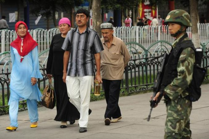 Китайский полицейский наблюдает за семьёй уйгуров. Фото: PETER PARKS/AFP/Getty Images   Epoch Times Россия