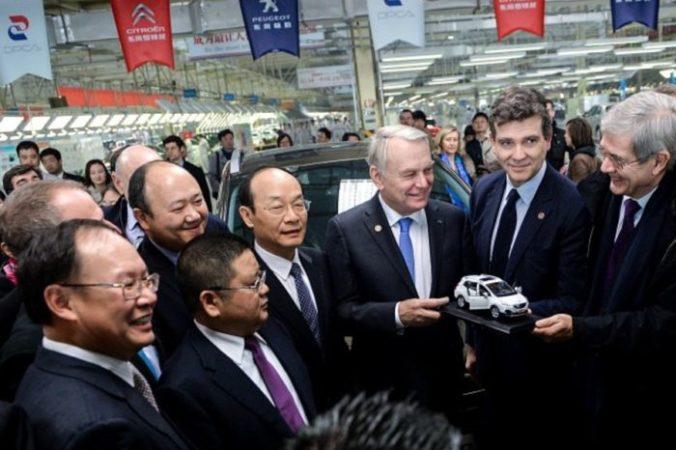 Экс премьер-министр Франции Жан-Марк Айро (третий справа) представляет модель автомобиля китайским менеджерам во время посещения автомобильного завода Dongfeng Peugeot-Citroën 7 декабря 2013 года в Ухане, Китай. Фото PETER PARKSAFPGetty Image | Epoch Times Россия
