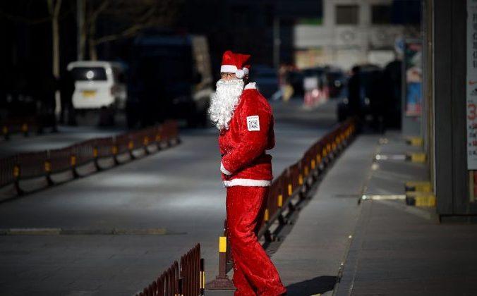 Продавец в костюме Санта-Клауса ждет покупателей у входа в магазин. 25 декабря 2014 года. Пекин. Wang Zhao/AFP/Getty Images | Epoch Times Россия