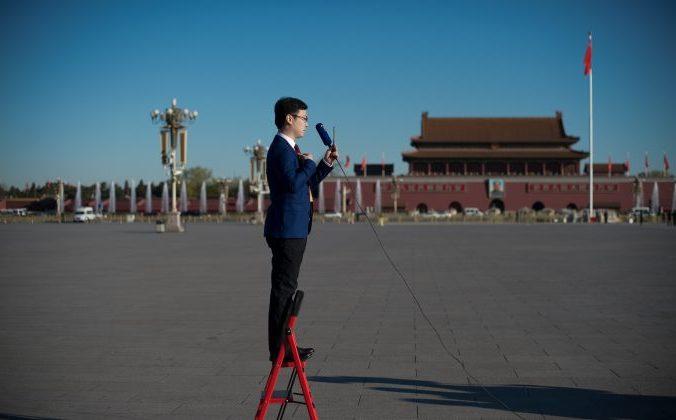 Журналист стоит на лестнице во время репортажа на площади Тяньаньмэнь в Пекине. 13 марта 2017 года. Фото: Nicolas Asfouri/AFP/Getty Images | Epoch Times Россия