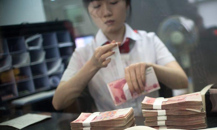 Сотрудник отделения Промышленно-коммерческого банка China Ltd (ICBC) считает деньги, обслуживая клиента 24 сентября 2014 г. (JOHANNES EISELE / AFP / Getty Images)   Epoch Times Россия
