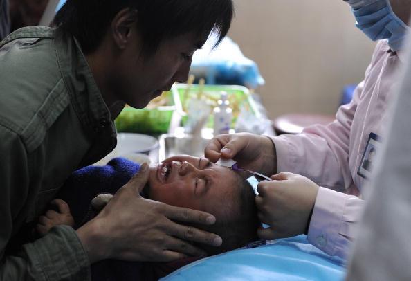 Мужчина держит сына, помогая медсестре делать ребенку инъекцию в больнице города Хэфэй провинции Аньхой. 7 апреля 2010 год. Фото: STR/AFP/Getty Images   Epoch Times Россия