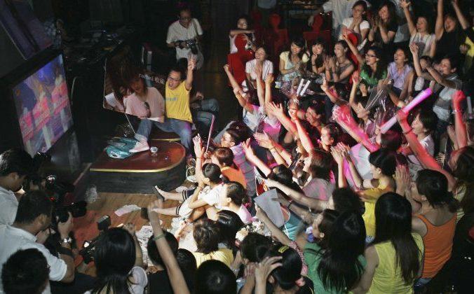 Поклонники телешоу Super Girl Voice болеют за своих любимых конкурсанток в баре. 26 августа 2005 год, Шанхай, Китай. Фото: China Photos/Getty Images   Epoch Times Россия