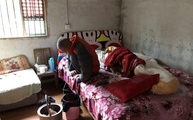 Страдающий силикозом Ван Чжаохун сидит на кровати в своей комнате уезда Санчжи, провинции Хунань. 27 ноября 2018 года, Китай. Фото: Sue-Lin Wong/Reuters | Epoch Times Россия