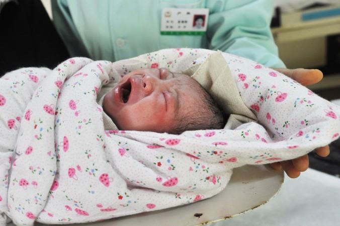 Новорождённый китайский мальчик, родившийся в районе Цзоупин в восточно-китайской провинции Шаньдун 31 октября 2011 г., стал 7-миллиардным жителем Земли. Фото: STR/AFP/Getty Images | Epoch Times Россия