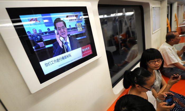 Телевизионный экран в поезде метро в Шанхае, 26 июня 2012 г. Китайский телеведущий раскритиковал фальсификацию рейтингов программ в материковом Китае на заседании Всекитайского собрания народных представителей 8 марта 2015 г. (Peter Parks / AFP / GettyImages)   Epoch Times Россия