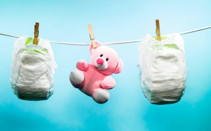 Детские подгузники и мягкая игрушка. Фото: JOEL SAGET/AFP/Getty Images | Epoch Times Россия