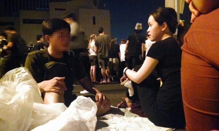 Молодой человек из материкового Китая (слева) обсуждает конкурирующие идеи о демократии в Гонконге с местной гонконгской женщиной 4 октября 2014 года. Движение оккупантов в Гонконге захватило ключевые дороги вокруг правительственных учреждений, стремясь к большей демократии. . (Мэтью Робертсон / Великая Эпоха)   Epoch Times Россия