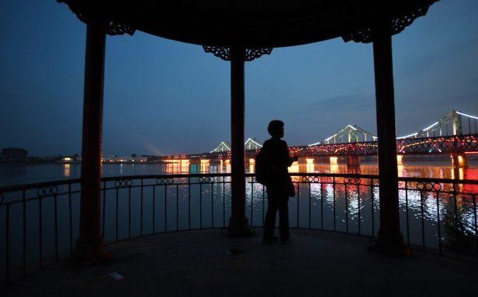 Женщина смотрит на китайский мост. Фото: Greg Baker/AFP/Getty Images | Epoch Times Россия