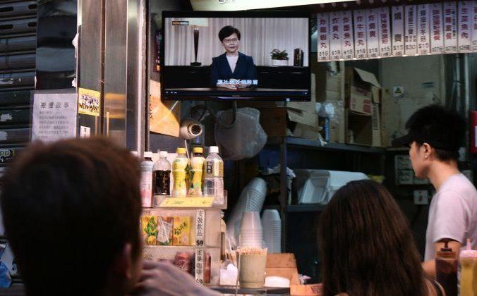 Люди в закусочной смотрят прямую телевизионную трансляцию, в которой исполнительный глава Гонконга Кэрри Лэм официально снимает спорный законопроект об экстрадиции. Гонконг, 4 сентября 2019 года. Фото: ANTHONY WALLACE/AFP/Getty Images | Epoch Times Россия