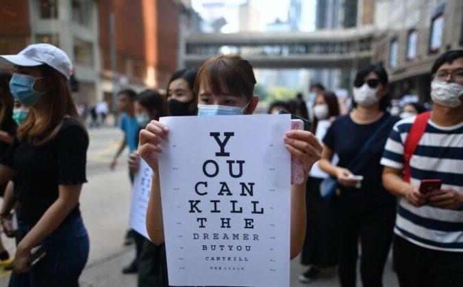 Протестующая держит плакат, имитирующий глазную диаграмму с надписью «Вы можете убить мечтателя, но не можете убить мечту», во время митинга в Чейтер-Гардене, Гонконг, 2 октября 2019 года. Фото: RASFAN/AFP via Getty Images | Epoch Times Россия
