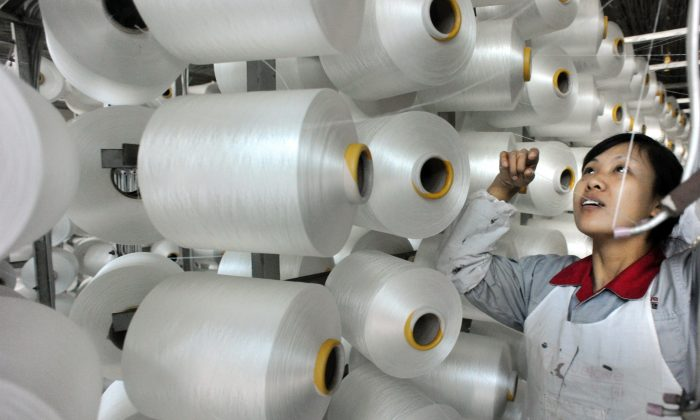 Китайский рабочий проверяет машину для производства одеял на экспорт на фабрике в Иу, провинция Чжэцзян, 12 января. (STR / AFP / Getty Images) | Epoch Times Россия
