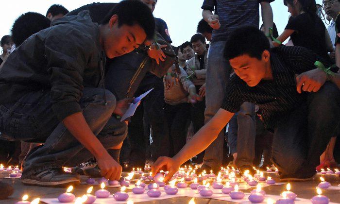Китайские добровольцы зажигают свечи на Мемориальной площади Таншаньского землетрясения во время церемонии поминовения жертв землетрясения в провинции Сычуань 21 мая 2008 г. (Саймон Лим / AFP / Getty Images) | Epoch Times Россия