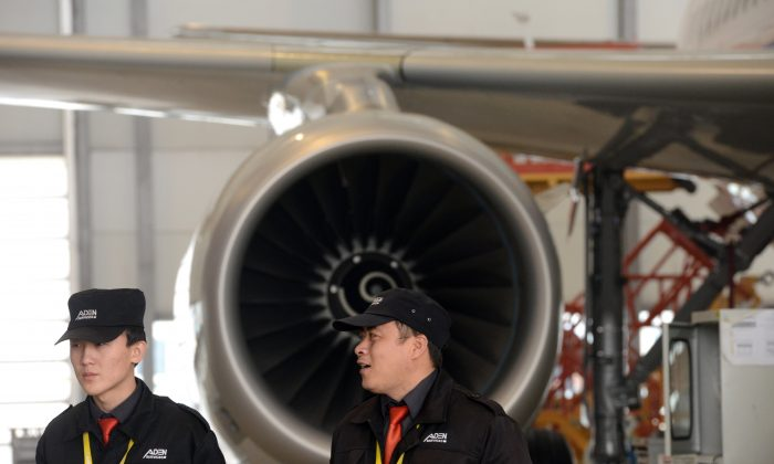 Китайские охранники стоят возле самолета Airbus A320, который собирается на сборочном заводе Airbus в Тяньцзине. Китай покупает европейские аэрокосмические компании, чтобы развивать свою аэрокосмическую промышленность. (ГОХ ЧАЙ ХИН / AFP / Getty Images) | Epoch Times Россия
