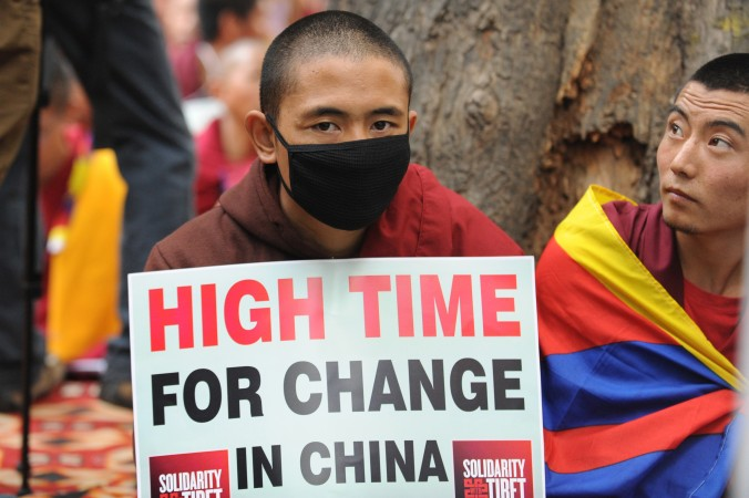 Тибетские монахи держат плакаты во время протестов в Нью-Дели, 31 января 2013 года. Китайские власти установили новую пограничную систему, которая усложнит для тибетцев побег в Непал. Фото: Raveendran/AFP/Getty Images | Epoch Times Россия