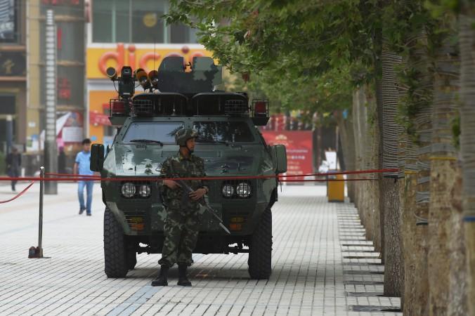 Полицейский из военизированной части стоит перед машиной в Хотане, Синьцзян. Фото: Greg Baker/AFP/Getty Images | Epoch Times Россия