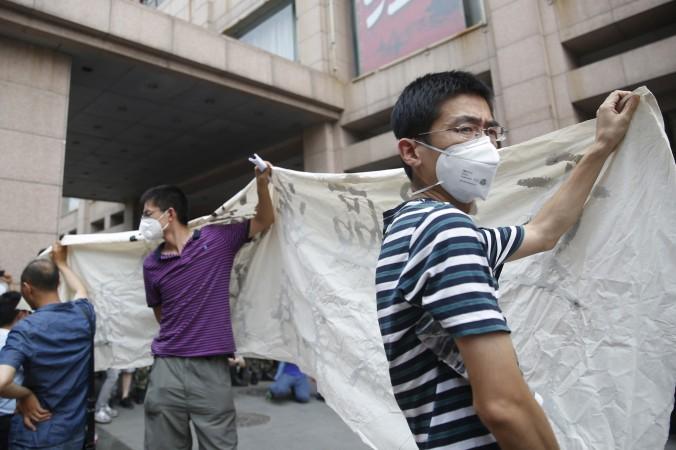 Пикет владельцев  домов, разрушенных  взрывом в Тяньцзине, во время пресс-конференции местных властей, 17 августа 2015 г., Тяньцзинь. Фото: STR/AFP/Getty Images   Epoch Times Россия