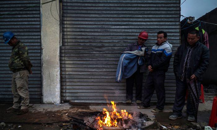 Рабочие греются у костра на разрушенной промышленной территории в городе Хоуцзе в Дунгуане, Китай, 26 января. (Лам Ик Фей / Getty Images)   Epoch Times Россия