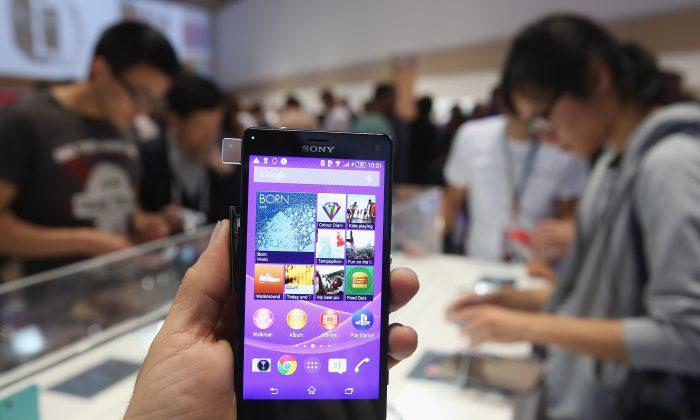 Фотограф держит смартфон Sony Xperia Z3 в Берлине, Германия. В смартфонах обнаружен зараженный файл, передающий данные в Китай. (Шон Гэллап / Getty Images) | Epoch Times Россия