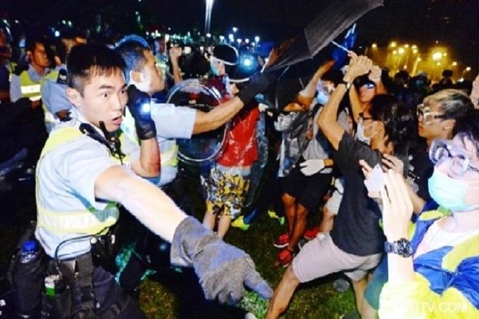 Протестующие защищаются зонтиками во время разгона в Гонконге. Фото: скриншот/ntd.tv   Epoch Times Россия