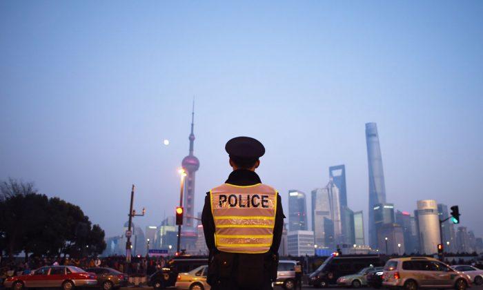 Офицер полиции охраняет место новогодней давки в Шанхае 3 января 2015 года. Власти Шанхая ужесточили цензуру в связи с этим инцидентом, заблокировав критику в Интернете, вызвав пользователей Интернета и подавив прессу. (Ван Чжао / AFP / Getty Images) | Epoch Times Россия