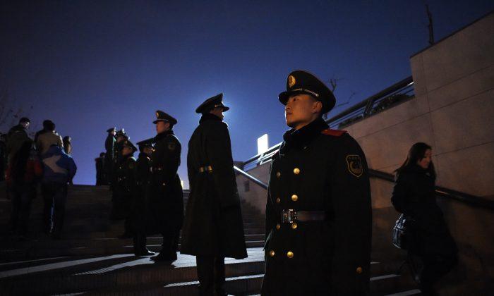 Группа полицейских стоит на страже в Шанхае 3 января 2015 года. 28 января полиция в провинции Гуйчжоу на юго-западе Китая тайно вскрыла тело жертвы, не уведомив его семью, а семья возмущенной жертвы обвинила полицию в краже его органов. (Ван Чжао / AFP / Getty Images) | Epoch Times Россия