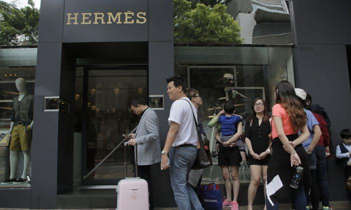 Туристы из материкового Китая выстраиваются в очередь возле бутика роскошных брендов в торговом районе Гонконга, 12 апреля 2015 г. (AP Photo / Vincent Yu)   Epoch Times Россия