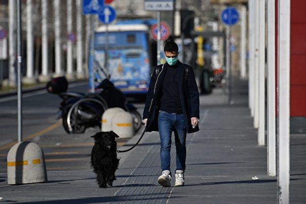 Человек в защитной маске выгуливает собаку в Турине, 10 марта 2020 года, Италия MARCO BERTORELLO/AFP via Getty Images   Epoch Times Россия