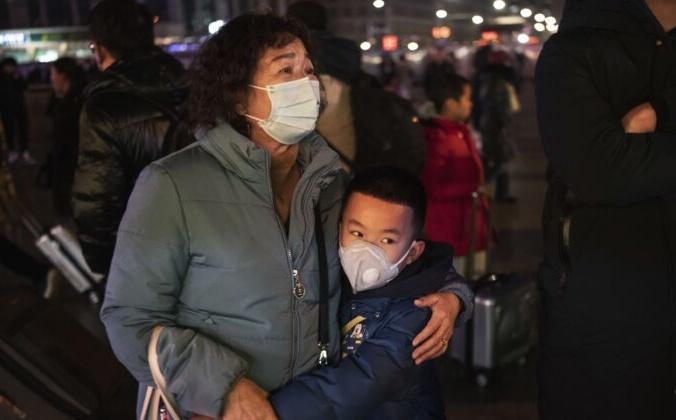Женщина с ребёнком на железнодорожном вокзале в Пекине, Китай, 21 января 2020 года. Kevin Frayer / Getty Images | Epoch Times Россия