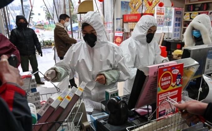 Работники аптек в защитной одежде и масках обслуживают клиентов в Ухане 25 января 2020 года. HECTOR RETAMAL/AFP via Getty Images   Epoch Times Россия