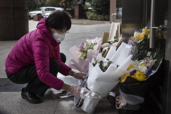 Местная жительница принесла цветы к госпиталю Ли Вэньляна, чтобы почтить его память, 7 февраля, 2020.Getty Images   Epoch Times Россия