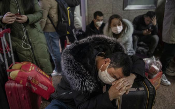 Китаец в защитной маске спит перед посадкой в поезд в Пекине, Китай, 23 января 2020 года. Kevin Frayer / Getty Images | Epoch Times Россия