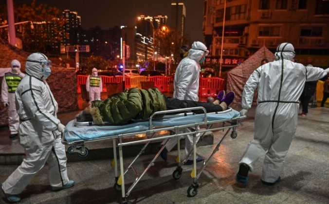 Медицинские работники в защитной одежде доставили пациента в больницу Красного Креста в Ухане, Китай, 25 января 2020 года. HECTOR RETAMAL/AFP via Getty Images | Epoch Times Россия