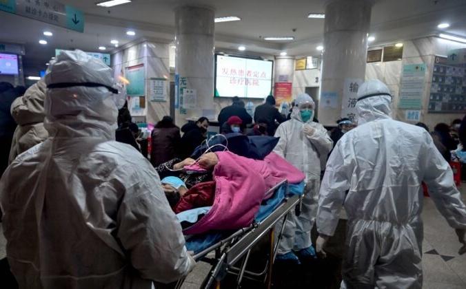 Медицинский персонал в защитной одежде привёз пациента в Уханьскую больницу Красного Креста, Китай, 25 января 2020 года. HECTOR RETAMAL/AFP via Getty Images | Epoch Times Россия