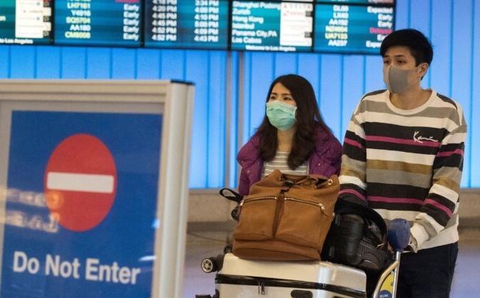Пассажиры в масках для защиты от коронавируса в международном аэропорту Лос-Анджелеса, Калифорния, 22 января 2020 года. MARK RALSTON/AFP via Getty Images | Epoch Times Россия