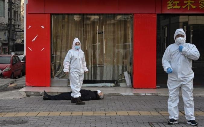Пожилой человек упал замертво на улице возле больницы в Ухане, Китай, 30 января 2020 года. HECTOR RETAMAL/AFP via Getty Images | Epoch Times Россия