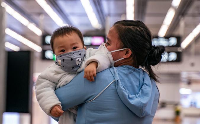 Женщина с ребёнком в защитных масках на железнодорожной станции в Гонконге, 29 января 2020 года. Anthony Kwan/Getty Images   Epoch Times Россия