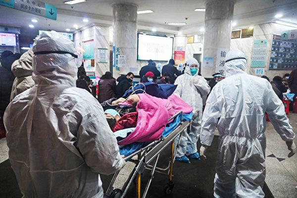 Медицинский персонал в защитной одежде прибыл с пациентом в больницу Уханьского общества Красного Креста, 25 января 2020 года. HECTOR RETAMAL/AFP via Getty Images | Epoch Times Россия